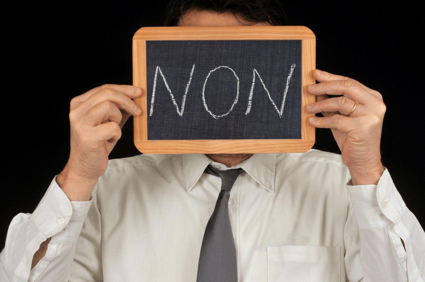 Un homme tient un mini tableau où on peut lire le mot NON écrit à la craie. C'est souvent la réponse aux nouvelles pratiques d'intervention sociale et à la difficulté à changer.